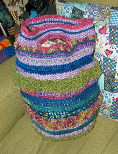 This crochet beast was made up from odds and ends of scrap yarn. (Note the patchwork cushion sneaking into the frame!)