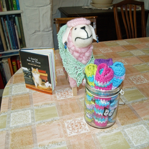 "Left to right: a poetry book ""written by cats"" called: I Could Pee on This; a candy-floss pink sheep ornament that I... um... customised? with a shawl and jewellery; and on the right a glass jar of wash cloths crocheted out of Lilys Sugar n Cream cotton."