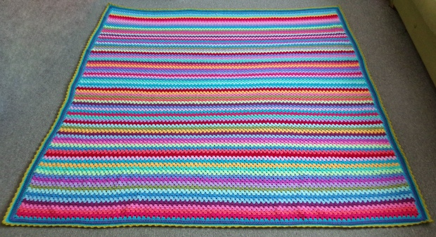 The Granny Stripe Beast of a blanket on a totally not photoshopped living room carpet